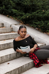 Black woman sitting on stairs reading