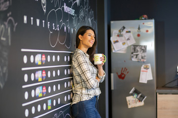 Young beautiful business woman drinking her coffee and smiling in the kitchen