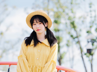 751fb070ef7 Outdoor portrait of beautiful young Chinese girl in yellow dress and straw  hat