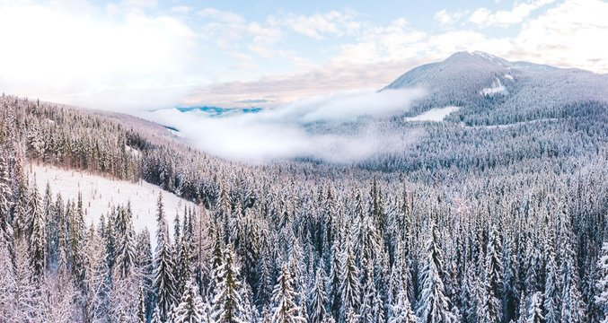 Aerial panorama of clouds low in snowy alpine valley