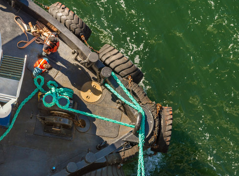 Overhead view of tugboat, ropes and workers assisting ship to dock, Alaska, USA.