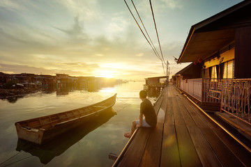 Young people watching the sunrise  on the jetties of Penang, Malaysia .