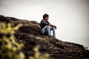 Young man in deep thoughts on top of the mountain