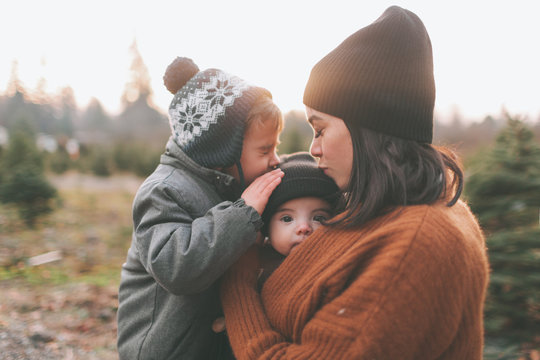 A mother and her son kissing a baby in winter.