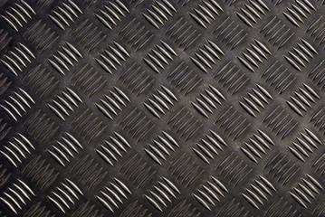 Dark shining metal floor surface with industrial diamond plate relief pattern