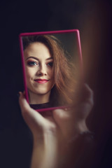 Caucasian girl looking into a mirror at herself.