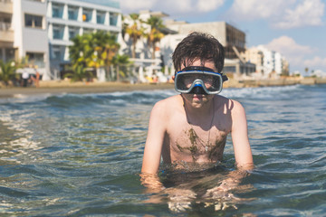 Happy and smiling boy in the snorkeling mask and tube on the resort town background. Travel and summer concept