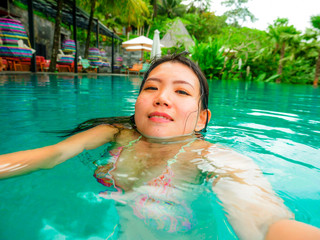 young happy and sweet Asian Korean woman swimming in tropical resort pool taking selfie portrait picture with mobile phone smiling excited and cheerful enjoying holidays