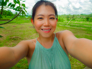 young happy and attractive Asian Chinese woman taking selfie self portrait with mobile phone at tropical island posing cheerful and relaxed exploring nature enjoying holidays