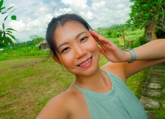 young happy and attractive Asian Korean woman taking selfie self portrait with mobile phone at tropical island posing cheerful and relaxed exploring nature enjoying holidays