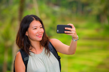 young happy and attractive Asian Chinese backpacker woman taking selfie self portrait with mobile phone at tropical island posing cheerful and relaxed exploring jungle