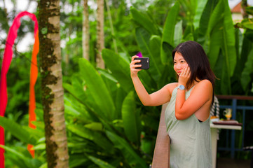 young happy and attractive Asian Korean woman taking selfie self portrait with mobile phone at tropical island posing cheerful and relaxed exploring jungle and nature