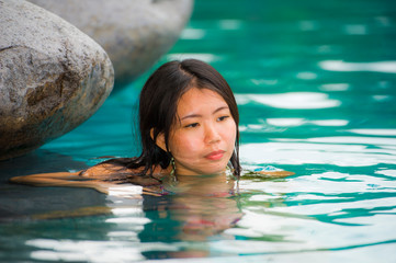 young attractive and beautiful Asian Chinese woman relaxing happy at tropical beach resort swimming at jungle infinity pool enjoying Summer holidays in paradise island