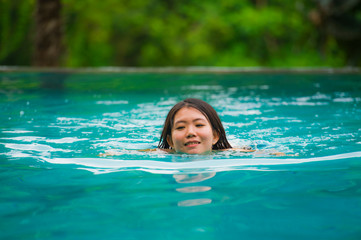 young attractive and beautiful Asian Korean woman relaxing happy at tropical beach resort swimming at hotel pool enjoying Summer holidays in paradise island