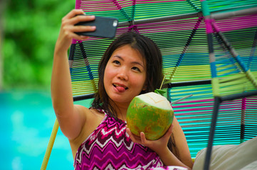 young beautiful and happy Asian Korean tourist woman drinking coconut water taking selfie picture with mobile phone at luxury tropical island resort swimming pool