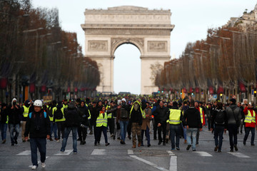 """Protesters wearing yellow vests walk on the Champs-Elysees Avenue with the Arc de Triomphe in the background during a national day of protest by the """"yellow vests"""" movement in Paris"""