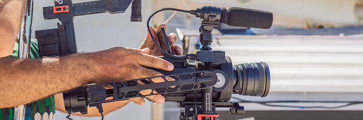 Steadicam operator prepare camera and 3-axis stabilizer-gimbal for a commercial shoot BANNER, LONG FORMAT
