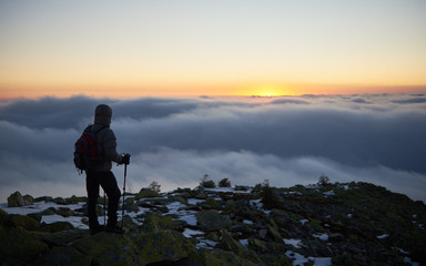 Back view of tourist in warm jacket with backpack and hiking sticks on rocky mountain peak on background of valley covered with white clouds stretching to horizon and bright morning sky at down.