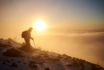 Tourist climber with backpack and trekking poles climbing on rocky snowy mountain steep slope on background of foggy valley filled with white puffy clouds, raising sun and blue sky at sunrise.