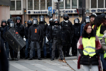 """French police secure a street as protesters wearing a yellow vest attend a demonstration by the """"yellow vests"""" movement in Paris"""