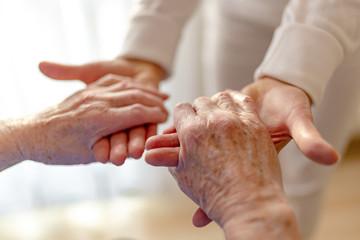 alte Frau wird von einer Pflegerin an den Händen gehalten