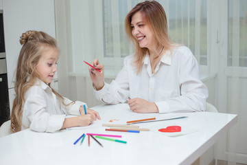 Mother and daughter are drawing together at home