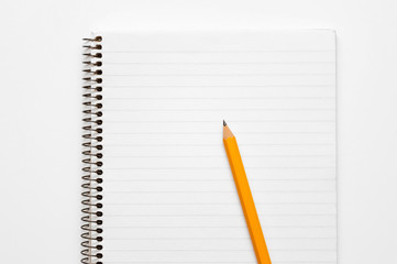Yellow pencil on a lined notepad on a spiral on a white background