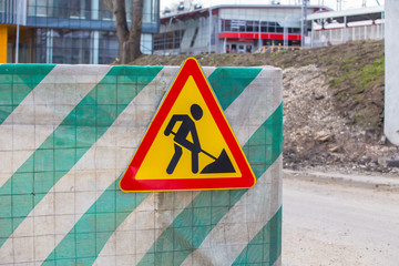 """road sign """"construction works"""" on the fence"""