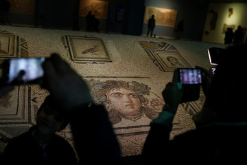 """Visitors take pictures of  the missing pieces of the historic """"Gypsy Girl"""" mosaic on display in an exhibition at their origin in Gaziantep"""