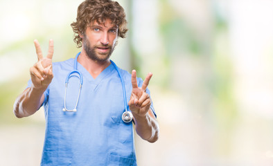 Handsome hispanic surgeon doctor man over isolated background smiling looking to the camera showing fingers doing victory sign. Number two.