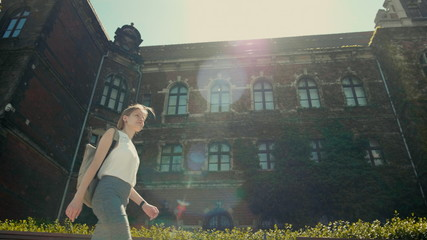 Slender Young Woman with Backpack is Walking along the Historic Building with Ivy in Summer with Nice Sun Rays and Lense Flare