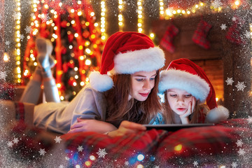 Christmas time. Smiling family mother and daughter in santas hats and pajamas watching funny video or choosing gifts on digital tablet while lie on the bed