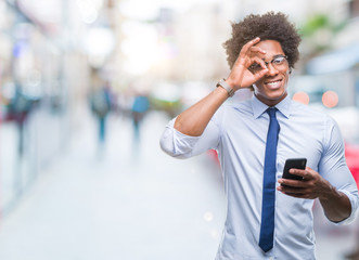 Afro american business man texting using smartphone over isolated background with happy face smiling doing ok sign with hand on eye looking through fingers