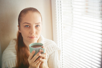 drinking tea sitting on the window of Caucasian beautiful middle-aged woman with red hair, toning