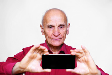 senior man in red shirt photographs on the phone, isolated on white background