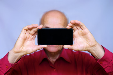senior man in a red shirt holding a smartphone in his hands in the face, photographs on the phone, isolated on white background