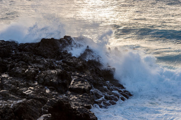 Strong wave meets lava rocks on the coast in the sunset