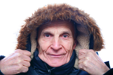 old senior man in a blue warm winter jacket, hands holding a fur hood, cold frosty weather