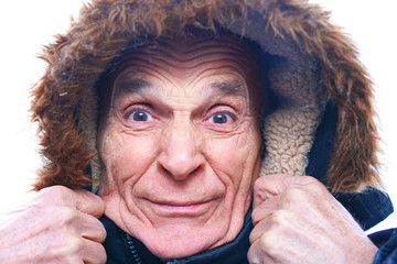 old senior man in a blue warm winter jacket, holding a fur hood with his hands, his face in wrinkles, shrank from a very strong frost, bad weather