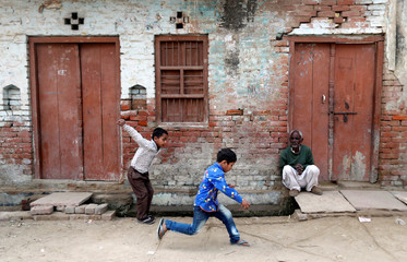 Children play as a man sits outside a house in Nayabans village