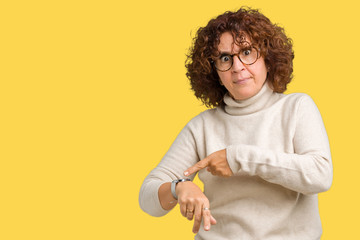 Beautiful middle ager senior woman wearing turtleneck sweater and glasses over isolated background In hurry pointing to watch time, impatience, upset and angry for deadline delay