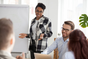Millennial African American mentor or coach interacting with office employees during flipchart presentation, multiethnic workers laugh brainstorming at meeting, having casual discussion or training