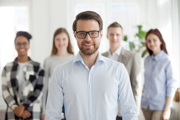 Happy successful businessman standing foreground with colleagues at background, smiling male employee posing looking at camera in office, man professional portrait with team at back