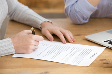 Close up of female job candidate sign contract after successful interview, woman put signature on document, finalize recruiting process, work applicant fill in paper business deal. Employment concept