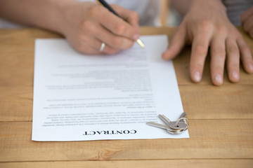 Close up of husband sign contract buying house from realtor or broker, man put signature on document, keys on table, taking mortgage or loan, renter finalize formal procedure closing deal with agent