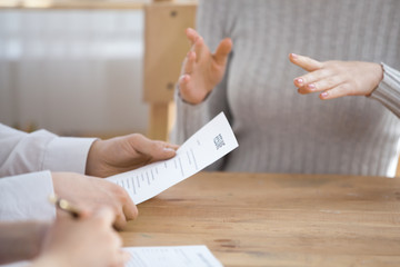 Close up of HR managers read candidate resume considering her candidature for open position, confident work applicant gesture talking with recruiters at business interview. Employment concept