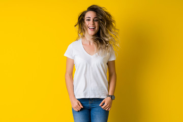 Beautiful young blonde woman jumping happy and excited over isolated yellow background