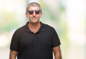 Handsome senior man wearing sunglasses over isolated background with serious expression on face. Simple and natural looking at the camera.