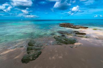Karibik pur, Sand und Felsen vor blaugrüner Wasserkulisse