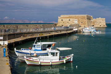 Fishing Boats under the walls of Koules Fortress in Heraklion. Fortress on the sea, tourist attraction of the city of Heraklion. Historic building in Crete, Greece.